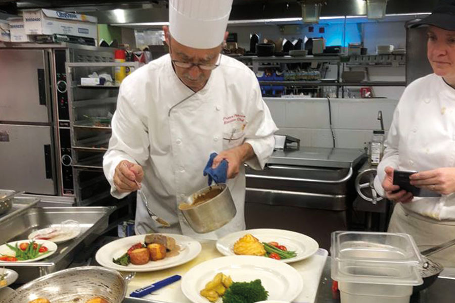 Chef Franco Paterno preparing a tasting meal in front of students.